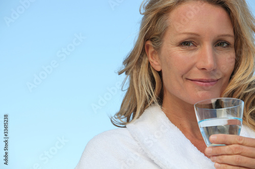 Attractive blonde haired woman drinking a glass of water - 33615238