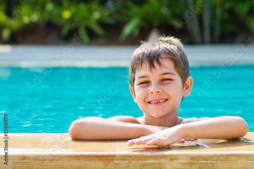 Happy young smiling boy in the pool