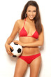 Pretty brunette woman in red bikini holding ball