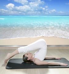 black mat yoga woman window view of tropical beach