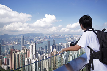 Tourist taking photo of Hong Kong skyline by his digital camera