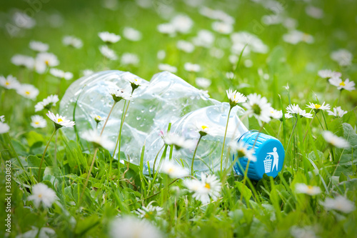 Plastic bottle on grass with recycle logo