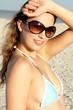 Sexy babe in bikini and sunglasses on maimi beach