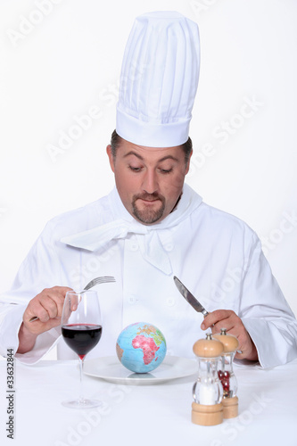 a chef cook watching a little globe in his plate