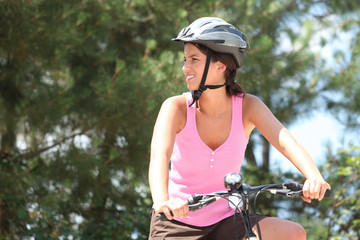 Young woman on a bike in the forest