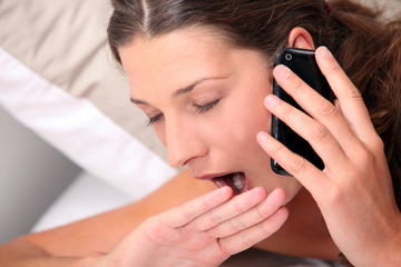 woman yawning on the phone