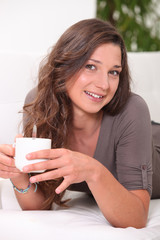 Young woman having a hot drink at home