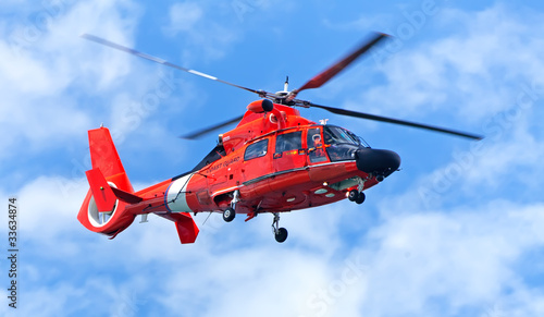 Red rescue helicopter moving in blue sky - 33634874