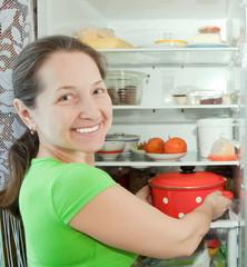 Mature woman putting pan into refrigerator