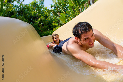 Father and Daughter Sliding Down Water Slide