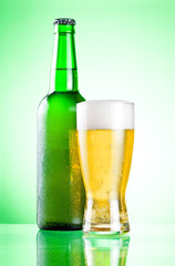 Chilled green bottle with condensate and a glass of beer lager o