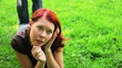 Redhaired woman relaxing on meadow