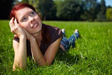 Verträumte Frau liegt im Gras
