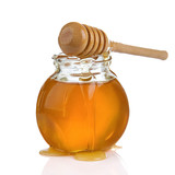 glass jar of honey and stick isolated on white