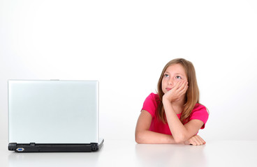 Girl with thoughtful look next to laptop computer