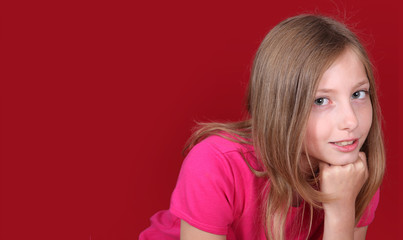 Portrait of beautiful blond girl on red background