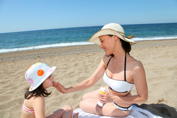 Mother putting sunscreen on her daughter's face