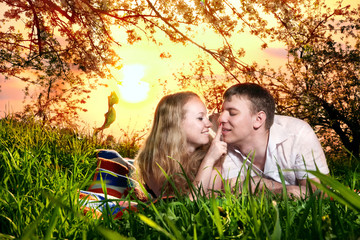 Couple on green grass at sunset