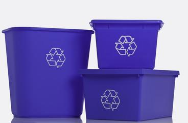 Three blue recycling bins