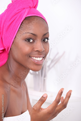 Woman in bathroom, drying hair