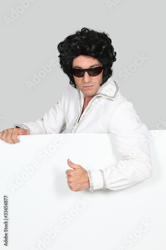 Man dressed as Elvis holding blank message board