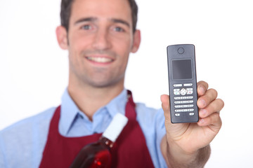 Wine waitor showing mobile phone
