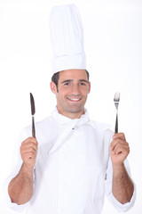 Chef in whites holding a knife and fork