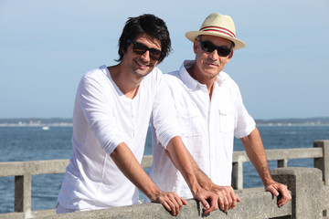 Father and son stood by waterfront