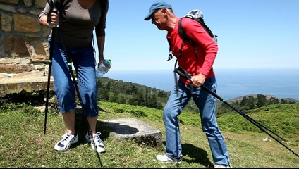 Senior hikers doing a break to drink water