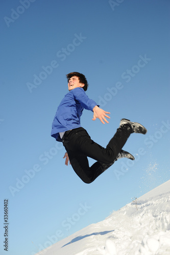 jumping teenager in blue shirt and black jeans
