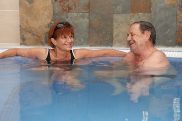 Elderly couple at hot water pool smiling