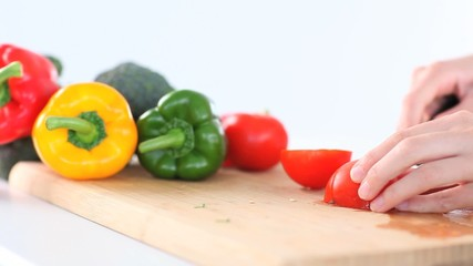 Feminine hands slicing peppers