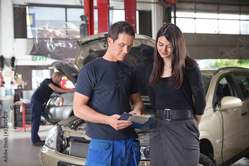 Mechanic showing the cost of service