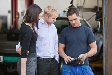 Mechanic standing with customers