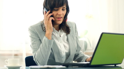 Attractive businesswoman talking on cellphone in office
