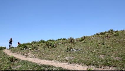 Senior couple riding mountain bikes in natural pathway