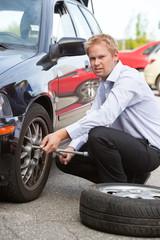Business Man Replacing Tire
