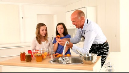 Grandfather making apricot jam with grandkids