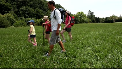 Family crossing country field on hiking day