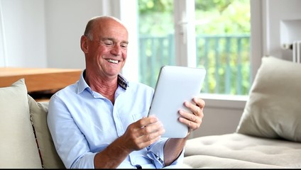Senior man sitting in sofa with electronic tablet