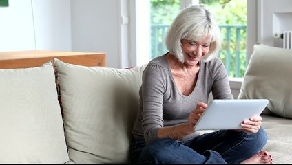 Senior woman sitting in sofa with electronic tablet