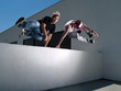 two male parkour free runners jumping over a wall