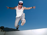 tattoed male parkour free runner jumping forward
