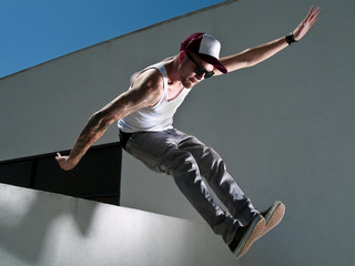 tattooed male parkour free runner jumping off a building