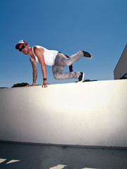tattooed male parkour freerunner climbing over a wall