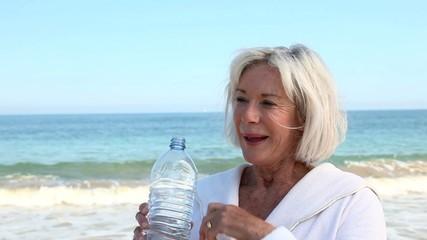 Senior woman drinking water from bottle