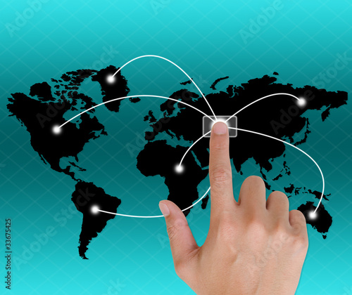 Hand pushing a button touch screen interface in wide world.