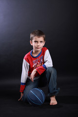 Boy of ten with a basketball ball on black background
