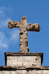 Old, weathered tomb stone cross against a blue sky