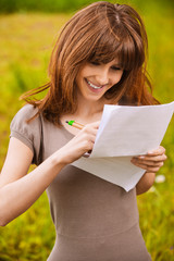 young beautiful smiling woman writing something
